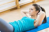 stock photo of flat stomach  - Attractive woman doing abs workout at gym for muscle toning and flat stomach - JPG