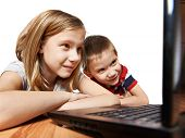 stock photo of fanny  - Children looking to laptop lying on the floor - JPG