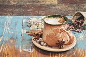 foto of spice  - Indian masala chai tea with spices and milk on rustic background - JPG