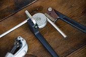 foto of bender  - Tube bender or pipe bender tools on wooden background - JPG