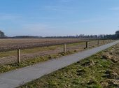 pic of bike path  - A paved bike path in perspective along a field lying fallow in Drenthe in the Netherlands - JPG