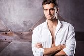 stock photo of undressing  - Handsome young man in unbuttoned shirt keeping arms crossed and looking at camera - JPG