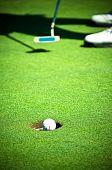 Golf ball entering the hole