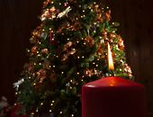 picture of candle flame  - Red candle and flame in front of a decorated Christmas tree - JPG