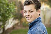 image of denim wear  - Smiling teenage boy outside wearing denim jacket horizontal format 13 yrs old - JPG