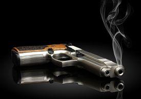foto of handgun  - Chromed handgun on black background with smoke - JPG