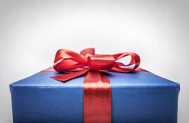 stock photo of bowing  - Blue gift box with red ribbon bow  - JPG