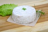 image of brie cheese  - Brie cheese with salad leaves on the wood background - JPG