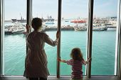 woman and her daughter standing and looking at ships in Qaboos Port through glass.