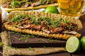 image of cheesesteak  - Steak sandwich with herbs lime and microgreens with little bit kick of hot sriracha souce - JPG