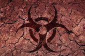 stock photo of biohazard symbol  - A biohazard symbol on cracked soil - JPG