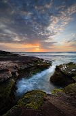 stock photo of algae  - Beautiful coastal sunrise with tidal ocean flows into craggy eroded rock channel growing green and red moss or algae - JPG