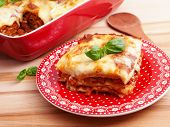 stock photo of lasagna  - Italian Lasagna Bolognese on a red plate shot from above - JPG