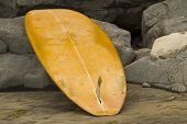 stock photo of boogie board  - Surfboard leaning on rocks at Swami - JPG