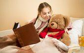 image of cute bears  - Portrait of cute brunette girl telling story to teddy bear at bed - JPG