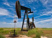 stock photo of nonrenewable  - Pumpjack at work in west Texas under blue cloudy skies - JPG