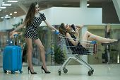 image of trolley  - Two cute attractive girls in dresses with shopping trolley and blue bag indoor on shop background horizontal picture