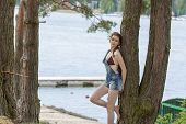 stock photo of jetties  - outdoor portrait of beautiful woman with bikini under overalls and braid hair - JPG