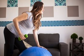foto of stability  - Attractive pregnant brunette exercising with dumbbells and a stability ball at home - JPG