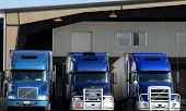 image of loading dock  - three blue semi truck tractors at loading dock - JPG