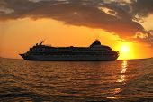 stock photo of cruise ship  - A cruise ship leaving a Hawaiian port at sunset  - JPG