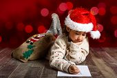 Постер, плакат: Adorable Little Girl Wearing Santa Hat Writing Santa Letter