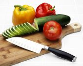 Knife, cutting board and vegetables