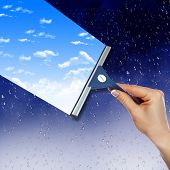 Hand with squeegee cleaning the  misted window