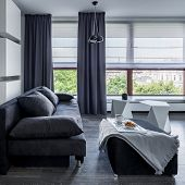 Gray Living Room With Sofa, Pouf Coffee Table And Big Windows With Blinds And Curtains poster