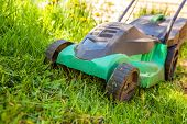 Lawn Mower Cutting Green Grass In Backyard In Sunny Day. Gardening Country Lifestyle Background. Bea poster