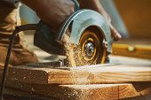 Close-up Of A Carpenter Using A Circular Saw To Cut A Large Board Of Wood A New Home Constructiion P poster