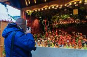 Постер, плакат: Man Taking Photos Of The Stall At Christmas Market At Kaiser Wilhelm Memorial Church In Winter Berli