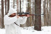 Sniper In White Camouflage Aiming With Rifle At Winter Forest.