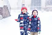 Two Little Kid Boys In Colorful Fashion Clothes Playing Outdoors During Strong Snowfall. Active Leis poster