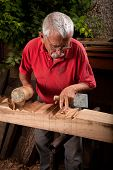 stock photo of woodcarving  - Old woodcarver working with mallet and chiesel - JPG