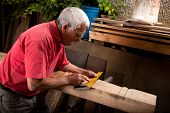 Old woodcarver working with mallet and chiesel