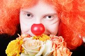 stock photo of clown rose  - Humble redhead clown with bunch of roses looking at us with kind smile - JPG