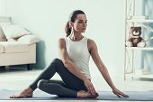 Young Beautiful Woman Doing Yoga Pose At Home. Attractive Woman In Sportswear Sitting On Yaga Mat In poster