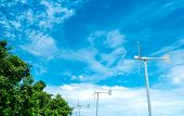 Horizontal Axis Wind Turbine With Blue Sky And White Clouds Near Green Tree. Wind Energy In Eco Wind poster
