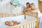 Happy parents near baby's bed