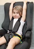 image of seatbelt  - Small girl sitting in a car safety seat with seatbelt - JPG