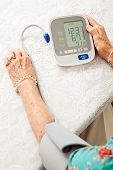 Senior woman using an automatic blood pressure cuff  to monitor her health at home.