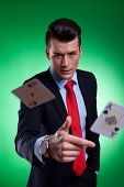 young business man throwing the winning hand , pair of aces, on green background