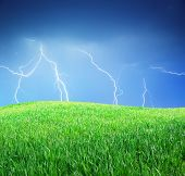 Lightning and green meadow. Nature composition.