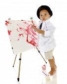 Um preschooler adorável olhando para o espectador como ele cria sua própria obra de arte pintada.  Ele ha