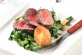Slices of roast beef with sauteed spinach