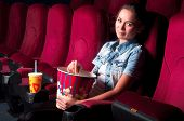 stock photo of cinema auditorium  - young attractive woman sitting in a cinema - JPG