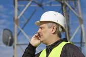 stock photo of relay  - Engineer talking on the cell phone near to gsm tower - JPG