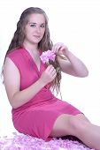 Girl In Pink Sitting With Flower