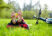 image of barefoot  - Cyclist on a halt reads lying in fresh green grass barefoot  - JPG